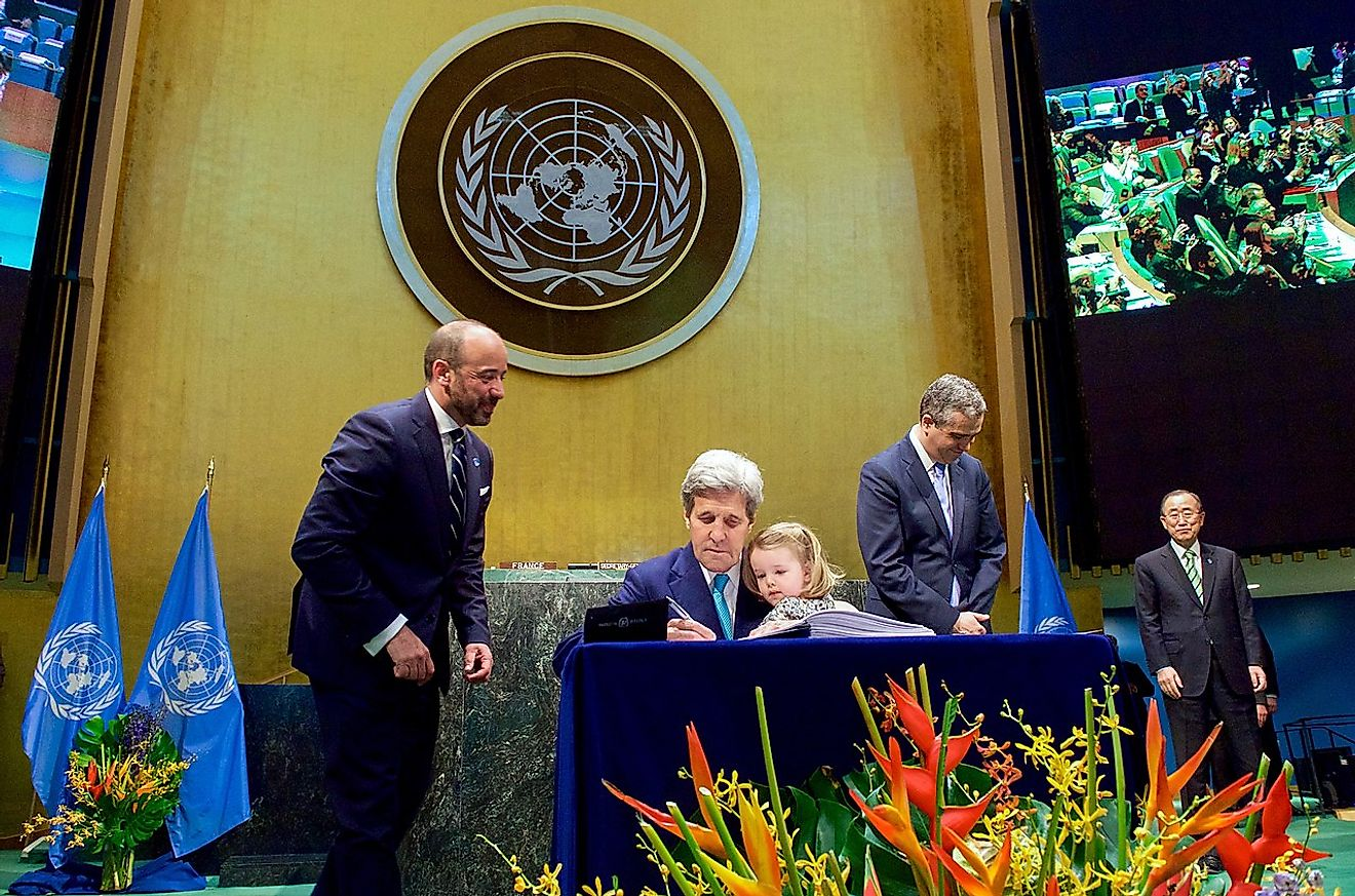 Secretary Kerry Holds Granddaughter Dobbs-Higginson on Lap While Signing COP21 Climate Change Agreement at UN General Assembly Hall in New York on Earth Day, April 22, 2016,. Image credit: U.S. Department of State from United States/Public domain.