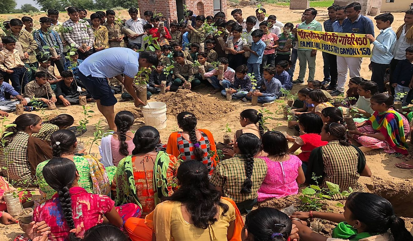 Jyani demonstrating a sapling planting technique to the children.