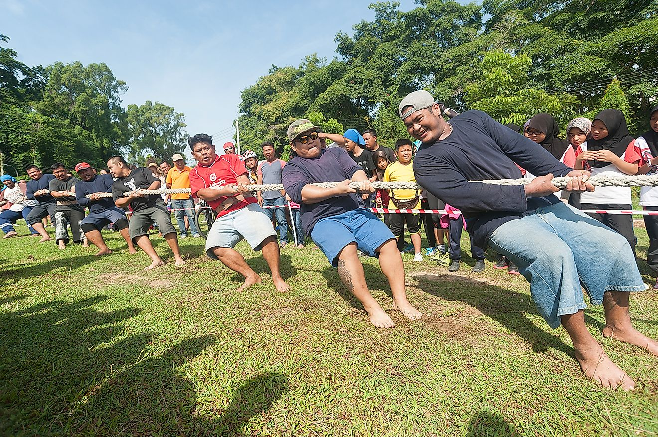 People participating in Tug Of War game during National Sports Day in Tuaran Public Field. Image credit: Lano Lan/Shutterstock.com