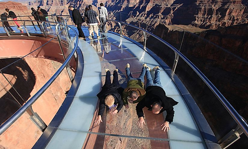 Visitors crawling along the skywalk at the Grand Canyon, one of the most thrilling skywalk experiences in the world.