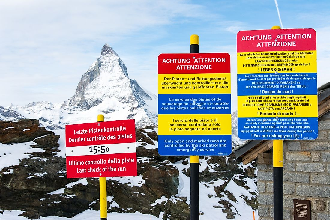 Signs in Switzerland using the country's three official languages. Editorial credit: Wirat Suandee / Shutterstock.com.