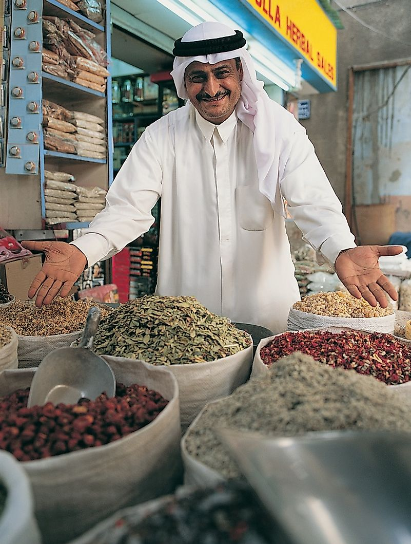 A vendor enthusiastically points out his goods in a souq in Dubai.