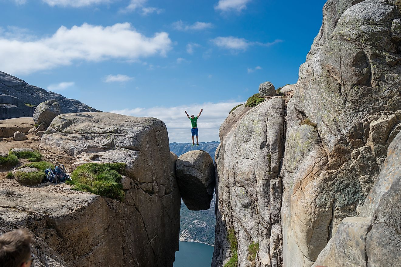 Man jumping over Kjeragbolten in Norway. Image credit:Viktor Hladchenko/Shutterstock.com