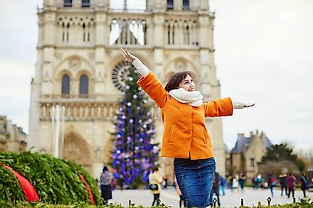 Happy young tourist in Paris on a winter day with main Parisian Christmas tree and Notre-Dame cathedral in the background. Image credit: Ekaterina Pokrovsky/Shutterstock.com