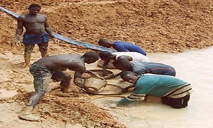 Diamond miners in Sierra Leone sifting through the sand in search of diamonds.