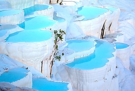 The vivid blue of Pamukkale's thermal pools contrast against the snow-white limestone formations.