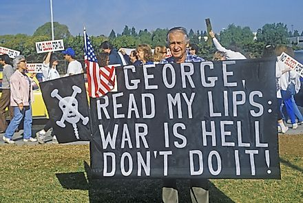 A man poses with a sign protesting the Iraq War. Editorial credit: Joseph Sohm / Shutterstock.com.