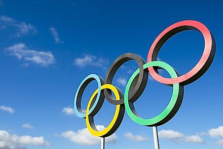 Olympic rings stand under bright blue sky in the Queen Elizabeth Olympic Park. Credit: lazyllama / Shutterstock.com