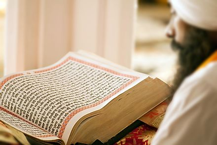 A holy man reading the Guru Granth Sahib, the holy book of Sikhism. Editorial credit: Tukaram.Karve / Shutterstock.com.