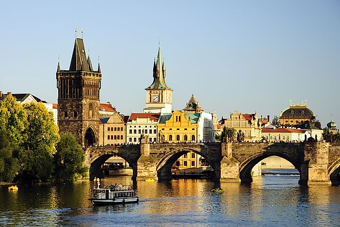View of Prague behind the Charles Bridge over the Vltava river.