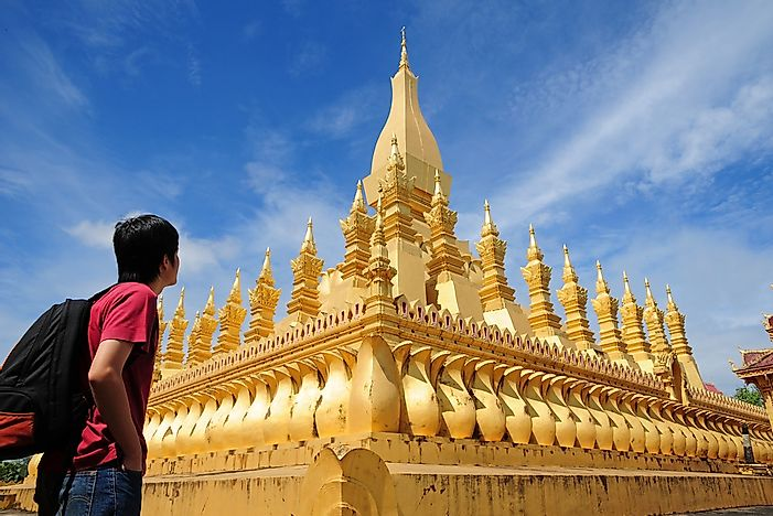 A backpacker stands outside of the Wat Pha-That Luang in Laos.