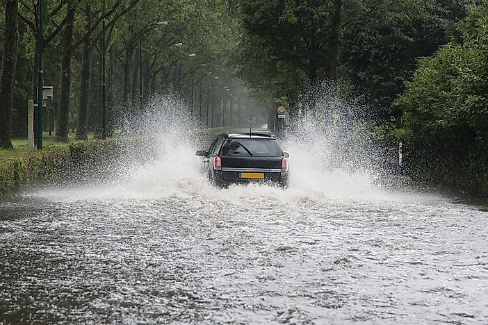 A car driving through a flooded street in the Netherlands.