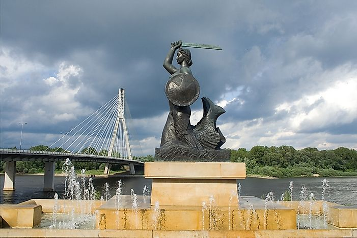The Warsaw Mermaid in front of the Swietokrzyski Bridge crossing the Vistula River.