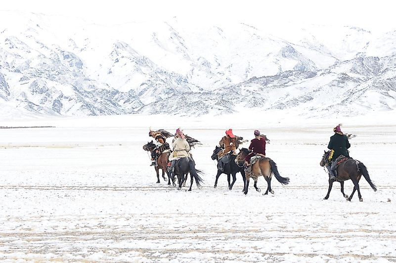 Golden eagle festival during the winter in Ulgi Mongolia local men riding on horses around the mountains covered with snow.
