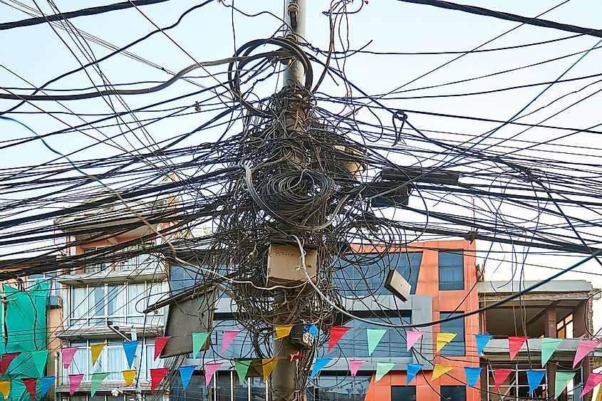 The chaos of cables and wires connections on the pole in Kathmandu, Nepal creating visual pollution. Image credit: Vladimir Zhoga/Shutterstock.com