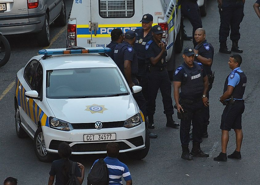 A group of Cape Town Metropolitan Police officers in various uniforms with a Metro Police vehicle. Image credit: Discott/Wikimedia.org
