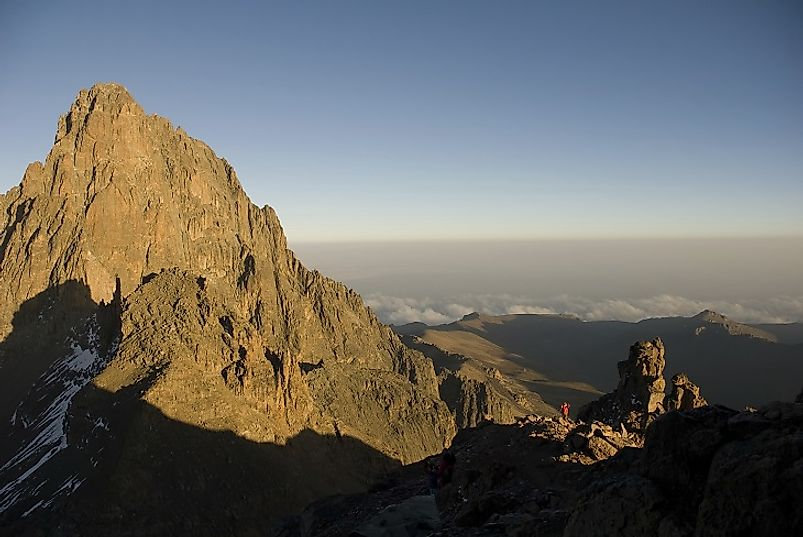 Note the man in the red shirt and others in the shadows (bottom right corner), dwarfed even by just the very peak of Mount Kenya.