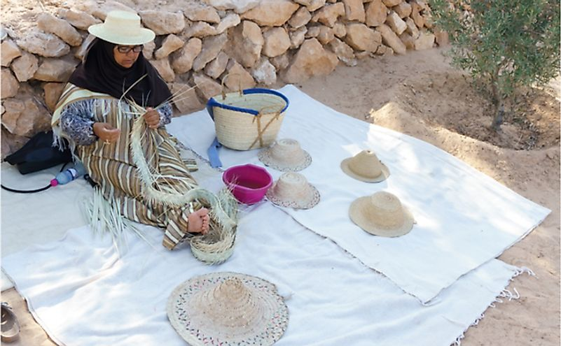 Arab woman engaged in weaving straw wide brim hat in Tunisia. Editorial credit: Pavel Kosolapov / Shutterstock.com