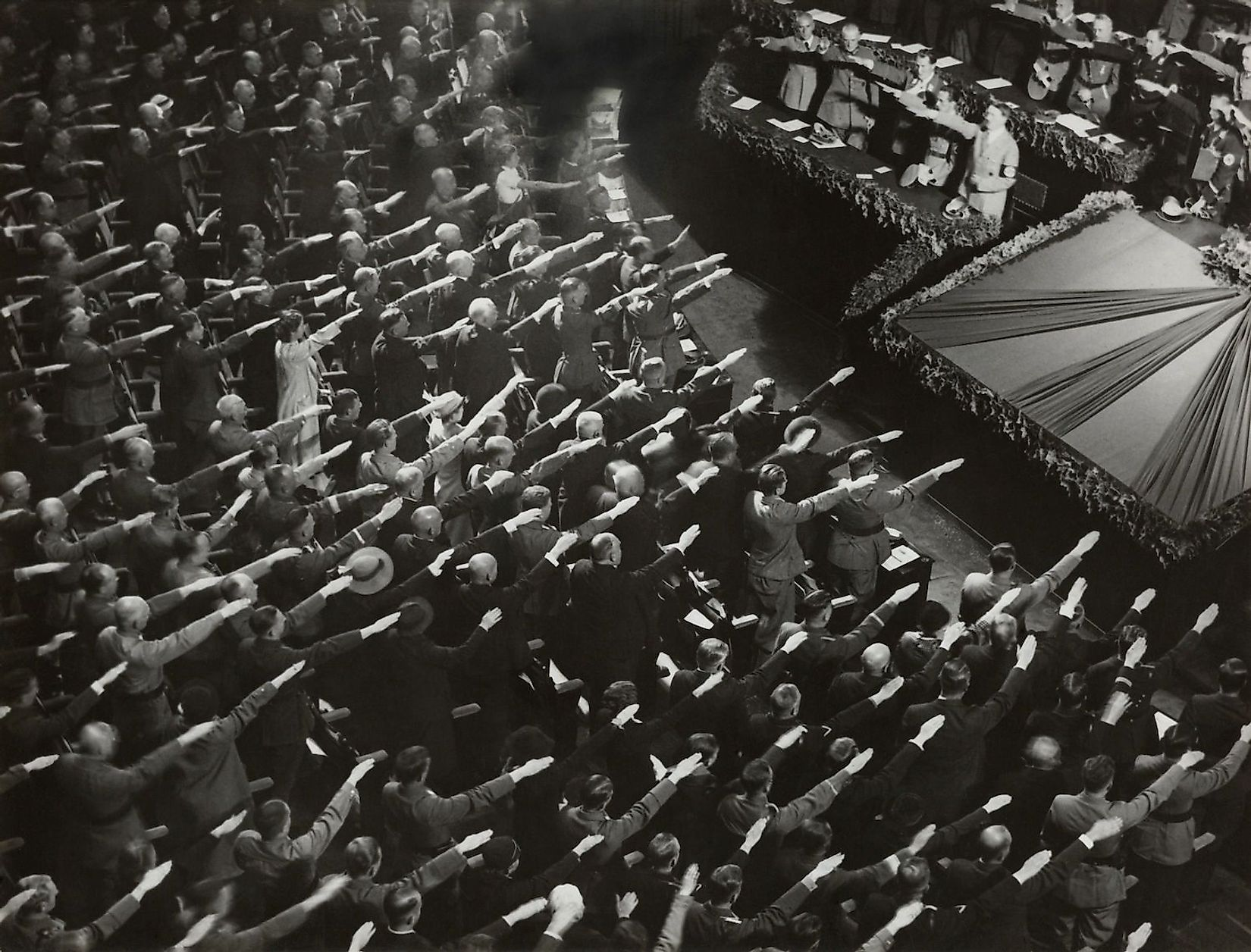 Attendees give Hitler the Nazi salute during the nation anthem, Oct. 9, 1935. They were meeting at the Kroll Opera in Berlin, to organize the Winter Relief festive to help finance charitable work. Image credit: Everett Collection/Shutterstock.com