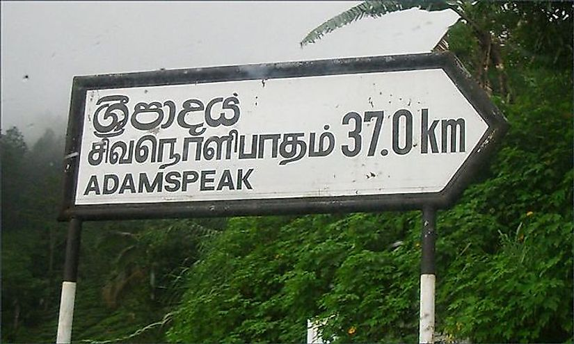 Place name sign in Sri Lanka in three languages with each linguistic version different from each other.