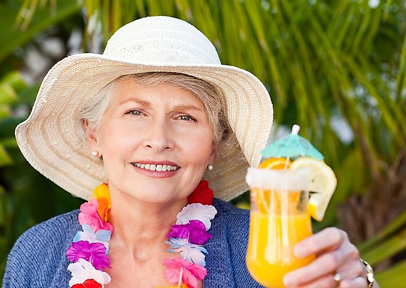 A female retiree enjoys a margarita at the beach in Mexico.
