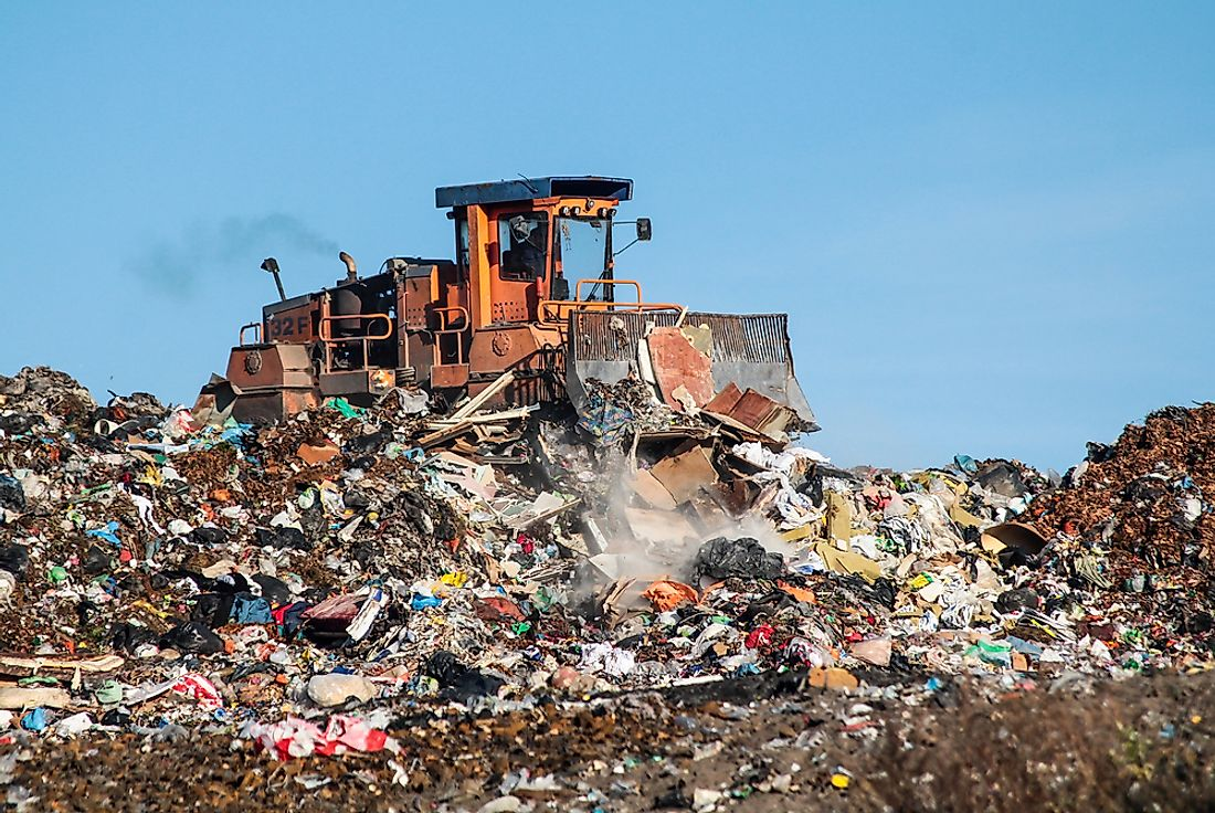 A large garbage dump and bulldozer.