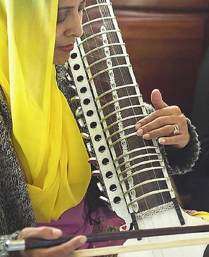 A woman plays a dilruba, a traditional Punjabi folk instrument.