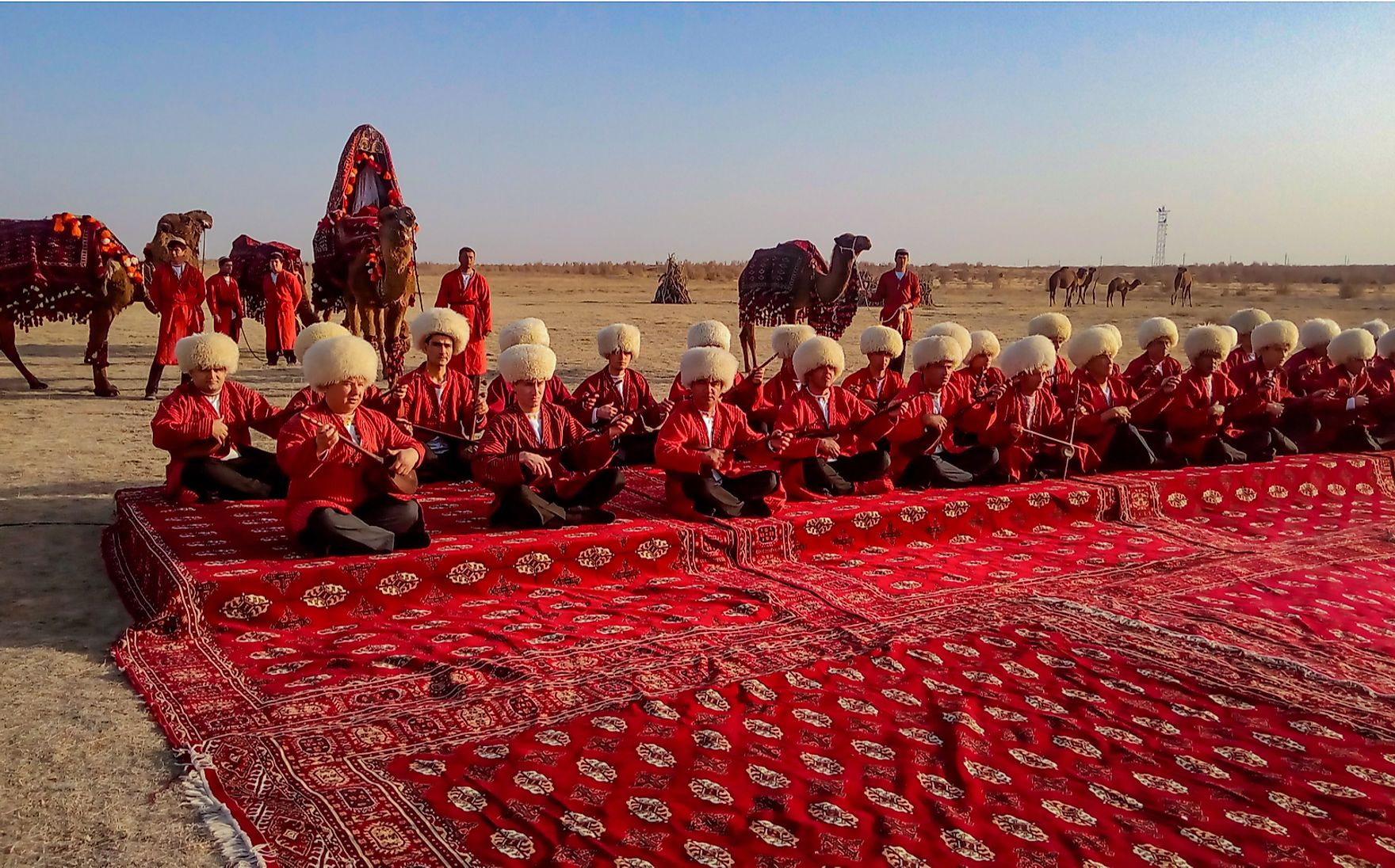 Turkmen sit on a traditional carpet playing musical instruments in Turkmenistan. Olga Nikanovich / Shutterstock.com.