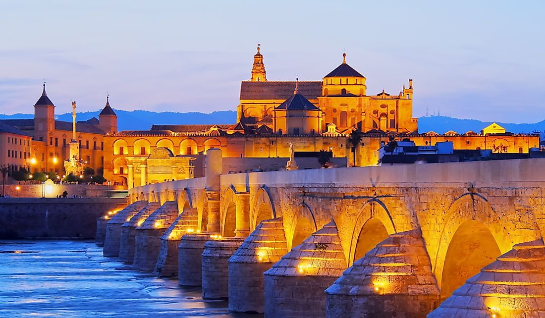 Night view of the Mosque-Cathedral of Cordoba and the Roman bridge in Cordoba, Andalusia, Spain.