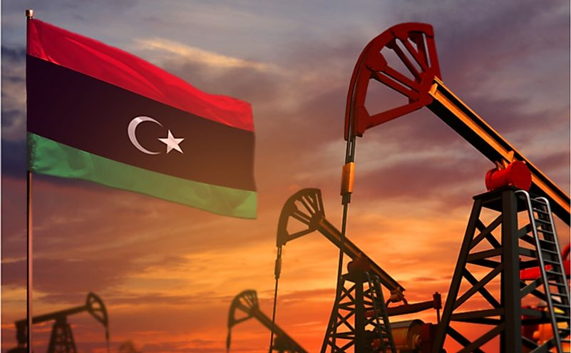 Libya flag and oil wells and the red and blue sunset or sunrise sky background.