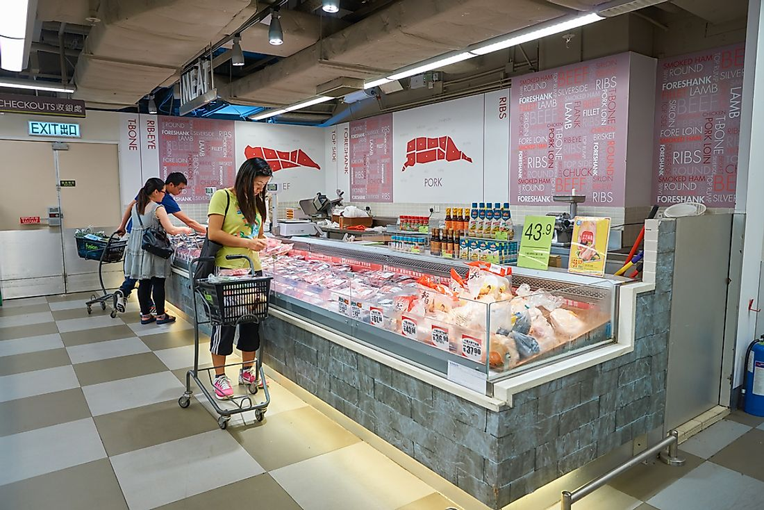 Women shop at a meat market in Hong Kong. Editorial credit: Sorbis / Shutterstock.com.