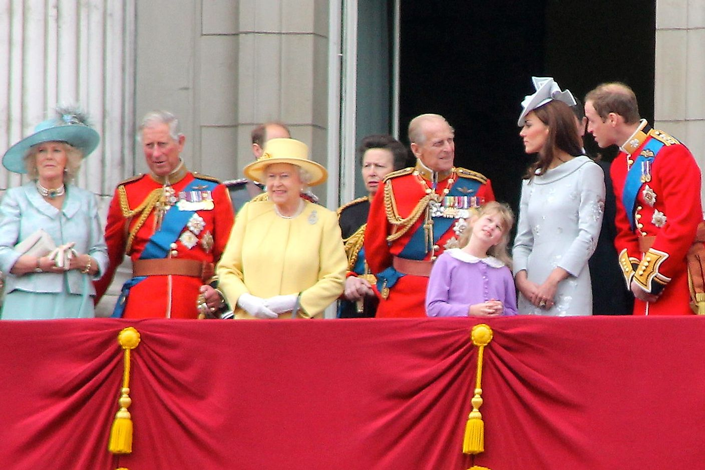 The British Royal Family with Queen Elizabeth II in the yellow dress.