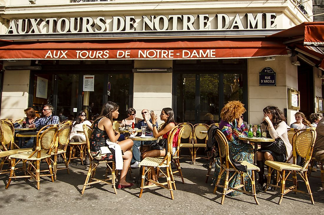 People sit in a cafe in Paris. Editorial credit: Rrrainbow / Shutterstock.com.
