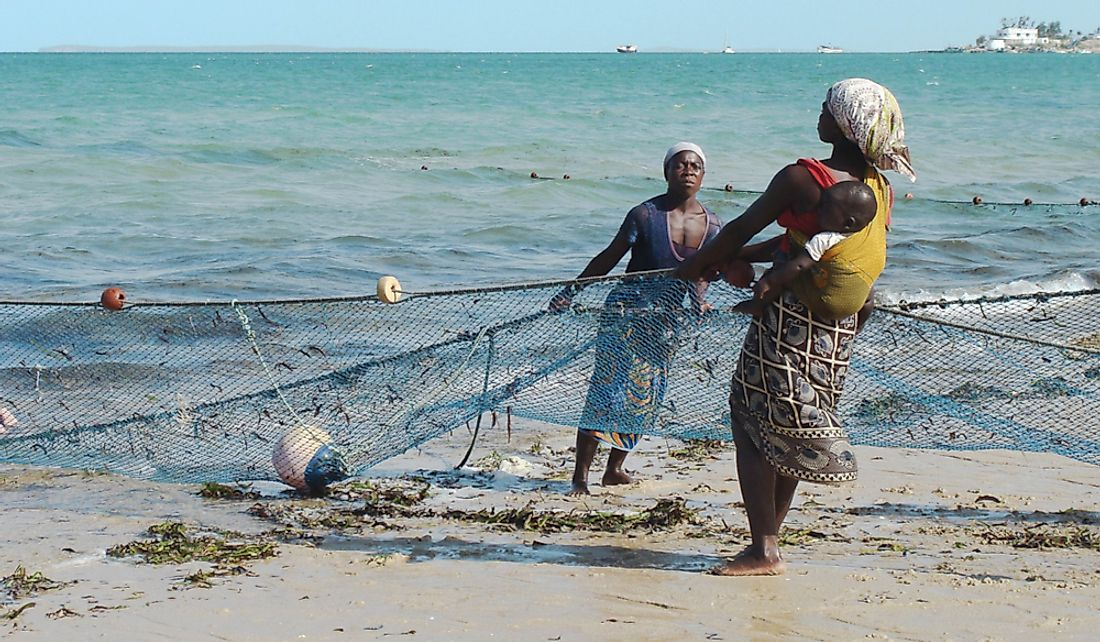 Women help pull in fishing nets in exchange for small fish in Vilanculos, Mozambique.  Editorial credit: Julia Kavtaradze / Shutterstock.com
