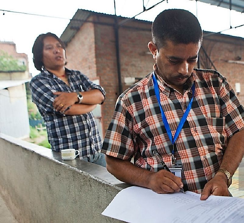 Nepalese carpet factory owners filling out forms to register their goods.