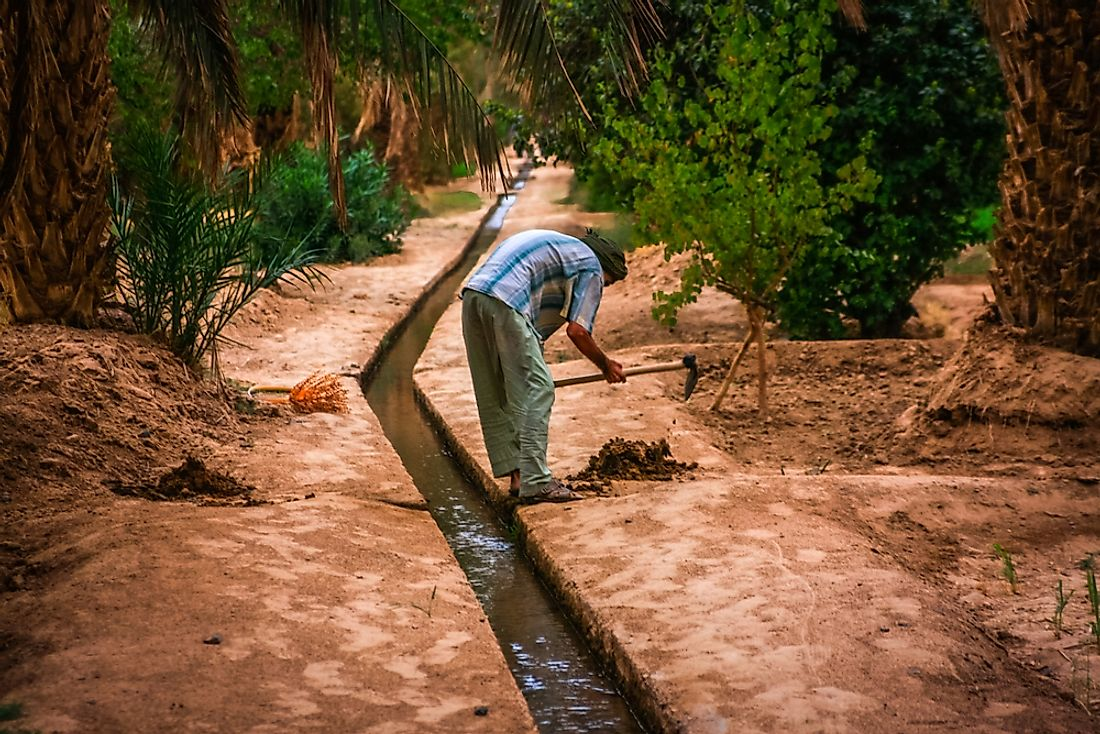 A man working on an irrigation canal in an oasis in the Sahara desert, Morocco.