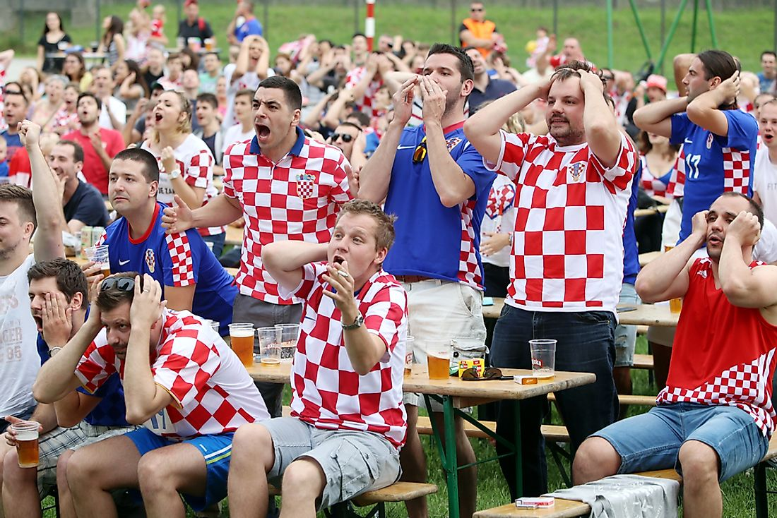 Croatian football fans cheer on a match.  Editorial credit: Goran Jakus / Shutterstock.com.
