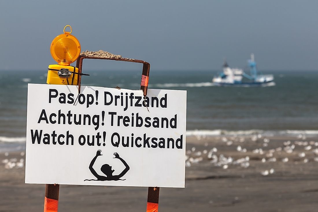 A sign warning of the danger of quicksand in multiple languages.