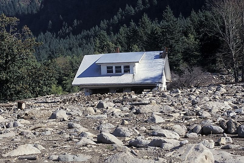 This house has been moved from its foundation and buried under debris by a mudslide.