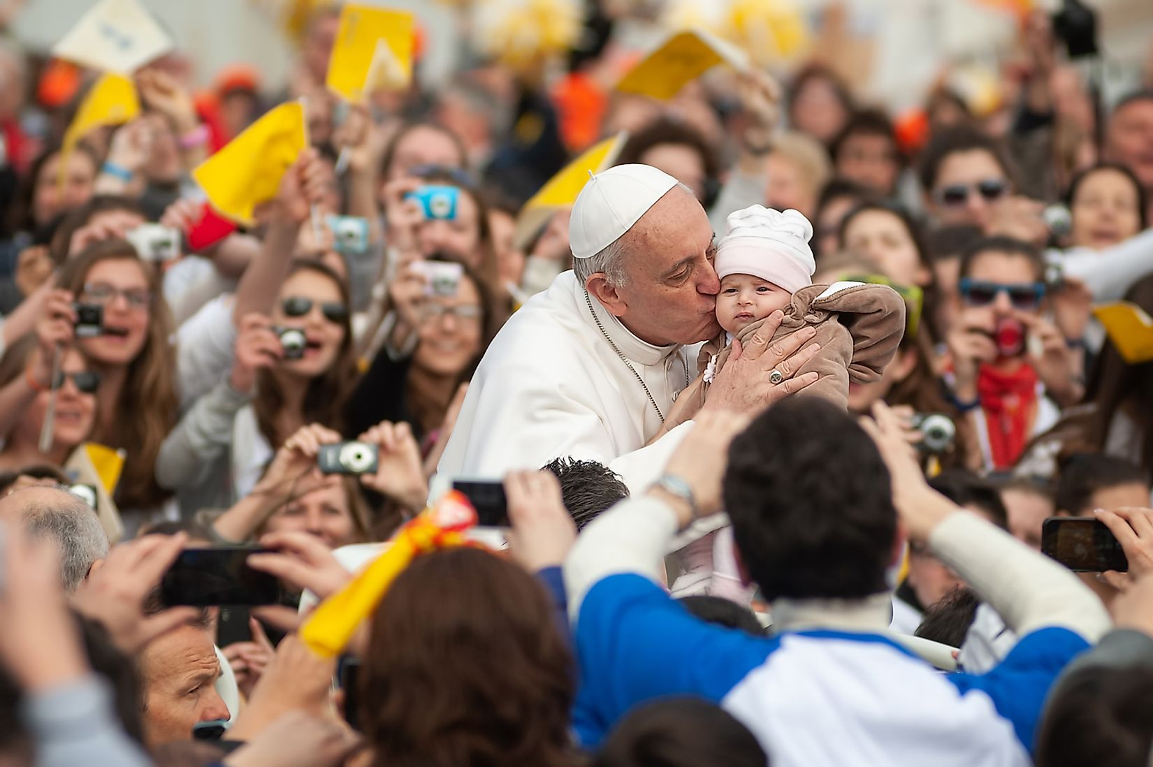 His Holiness Pope Francis I kisses a child during a prayer in front of St Peter' Basilica in Vatican City. Image credit: Boris Stroujko/Shutterstock.com