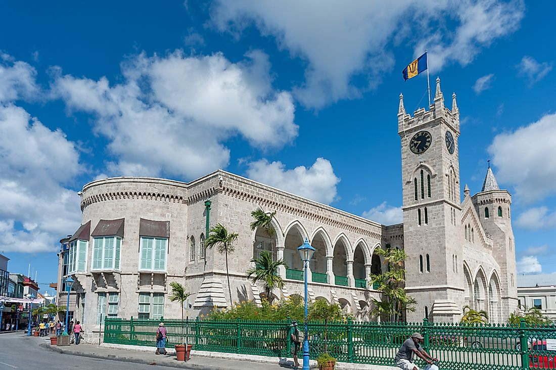 Flag of Barbados flying above the Parliament Buildings of Bridgetown, Barbados.  Editorial credit: photosounds / Shutterstock.com