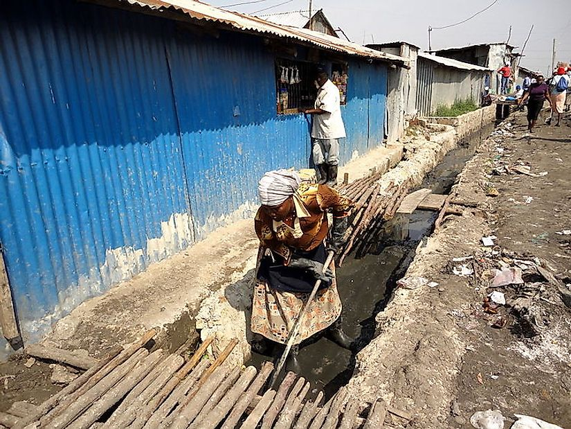 A woman cleaning drainage ditches in Kenya to discourage mosquito breeding and thus prevent malaria.