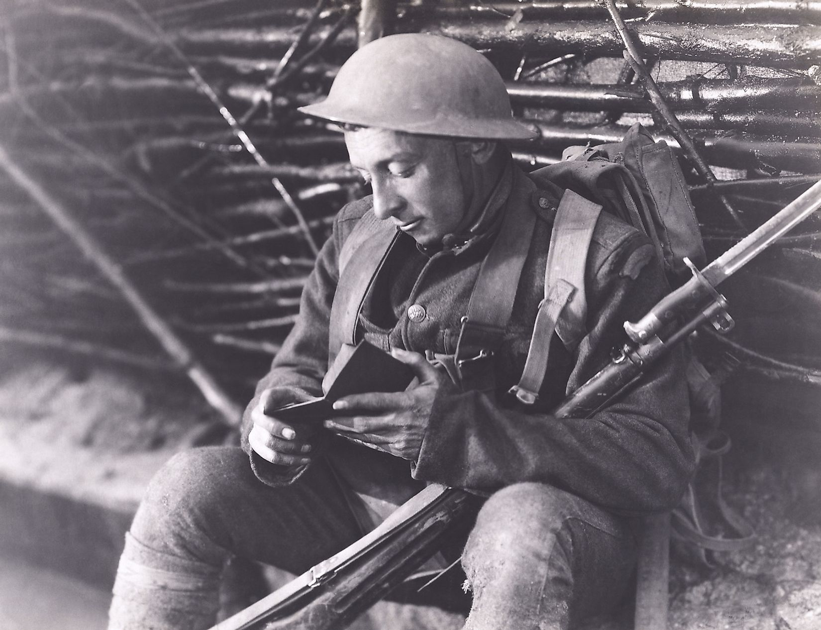 A World War soldier reading a book while posted at the warfront. Image credit: Everett Collection/Shutterstock.com