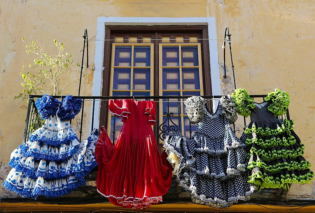 Traditional Spanish dresses hang from a balcony in Spain.