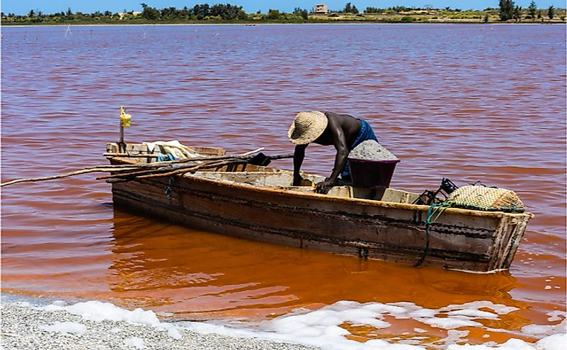 African man on the wooden boat over the Lake Retba or Lac Rose in Senegal.