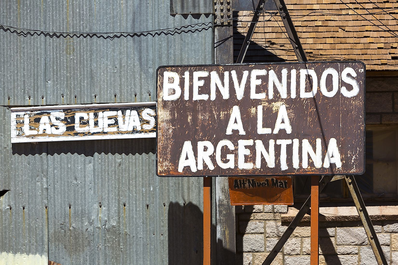Rusted old retro sign saying welcome to Argentina written in Spanish at an old train station at the border of Chile and Argentina near the Aconcagua National Park. Image credit: Watch the World/Shutterstock.com