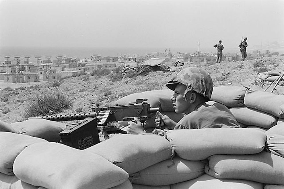 US Marine sits points a machine gun towards Beirut, Lebanon, in the distance.