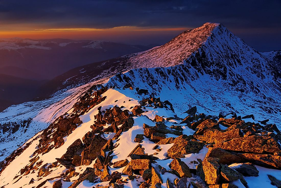 The sun sets over the majestic peaks of Retezat National Park in Romania.