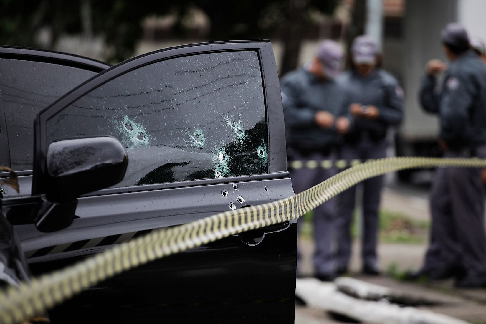Bullet holes are seen in the window of a car after an armed robbery in Sao Paulo, Brazil. Image credit: Nelson Antoine/Shutterstock.com