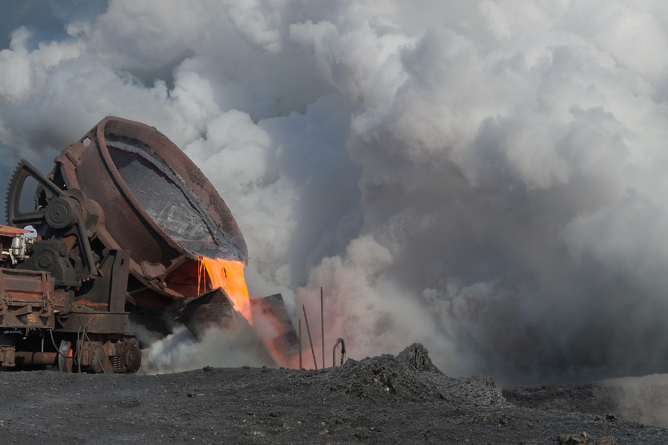 The liquid molten slag and a cloud of hot steam generated during the granulation of the slag polluting the land. Image credit: Nordroden/Shutterstock.com